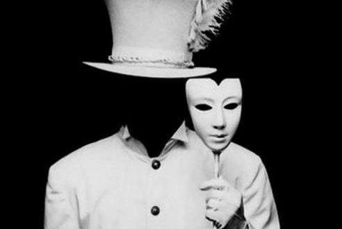 Persona che tiene in mano una maschera